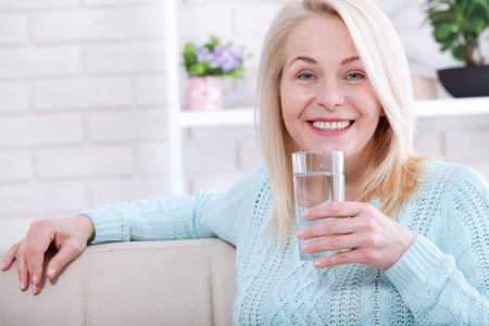 Photo pour Beautiful middle aged woman drinking water in the morning - image libre de droit