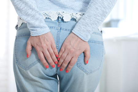 Photo pour Woman with haemorrhoids touching her butt with her hands - image libre de droit