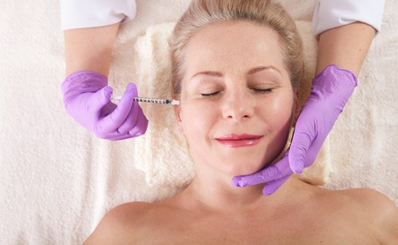 Photo pour Middle aged woman gets cosmetic injection in her wrinkles near the eyes. - image libre de droit