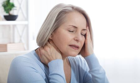Photo pour Woman suffering from stress or a headache grimacing in pain as she holds the back of her neck with her other hand to her temple, with copyspace. Concept photo with indicating location of pain. - image libre de droit