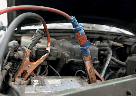 Close up of the old  jump leads wrapped by tape on a car flatten battery, outdoor shot with particular focus