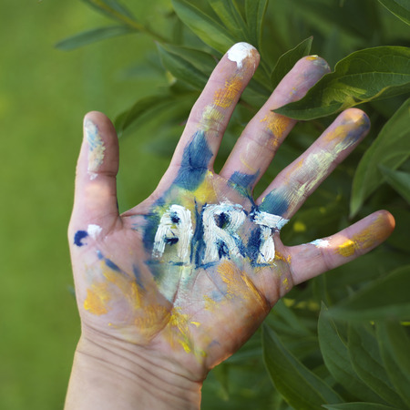 Photo pour Painted word Art on a human hand, green foliage in the blurred background, concept of visual arts - image libre de droit
