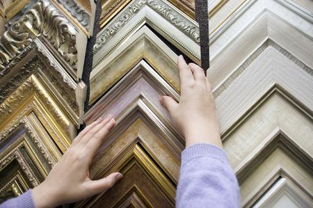 Photo pour Female hands arranging the frames samples in a framing workshop - image libre de droit