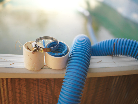 Foto de Swimming pool hose needs repair and hose clamp, outdoor close-up - Imagen libre de derechos