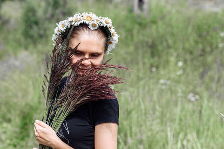 Photo pour young woman with a wreath of daisies on her head in the sun on a field of grass - image libre de droit