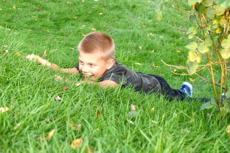 Photo pour The boy crawls in the green grass in the summer. Cheerful happy summer vacation outdoor. - image libre de droit