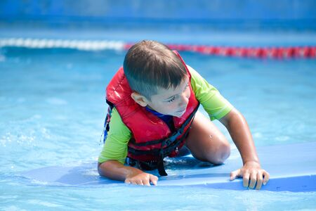 Photo pour Safe action in the pool. Life jacket on the boy. Saving the child from the water - image libre de droit