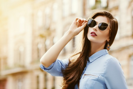 Outdoor portrait of a young beautiful confident woman posing on the street. Model wearing stylish sunglasses. Girl looking up. Female fashion. Sunny day. Close up. City lifestyle. Copy space for text
