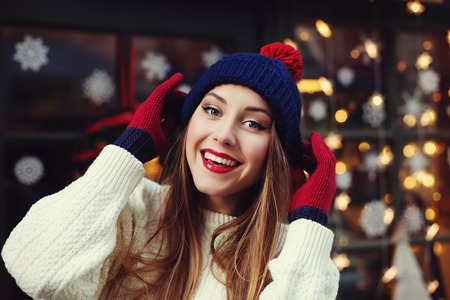 Photo pour Street portrait of smiling beautiful young woman wearing stylish classic winter knitted clothes. Model looking at camera, Festive garland lights. Close up. - image libre de droit