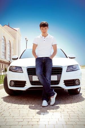 Photo pour Handsome man casually leaning against the car, outdoors - image libre de droit