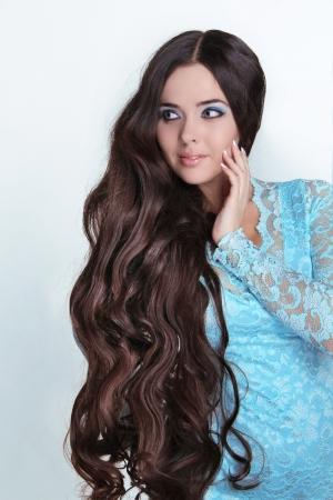 Beautiful Brunette Girl. Healthy Long Curly Hair. Lady in blue dress looking away