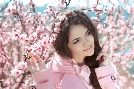 Beautiful young woman over pink blossom tree, outdoors portrait