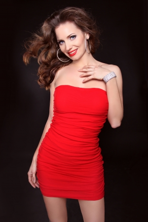 Beautiful smiling woman in red dress posing isolated on black background, studio shot の写真素材
