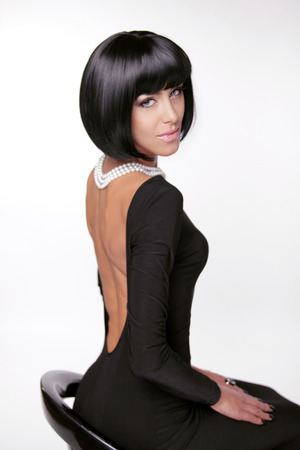 Brunette woman in sexy dress posing at studio. Vogue style. Fashion Haircut.