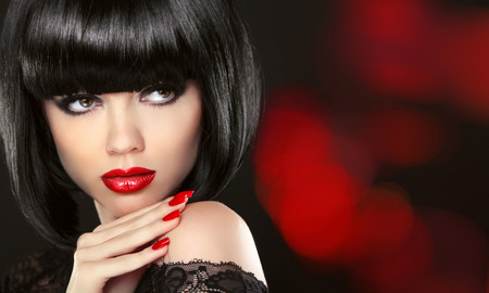 Beauty Fashion model girl portait. Makeup and red manicured nails. Bob black hairstyle. Brunette woman posing over black background.