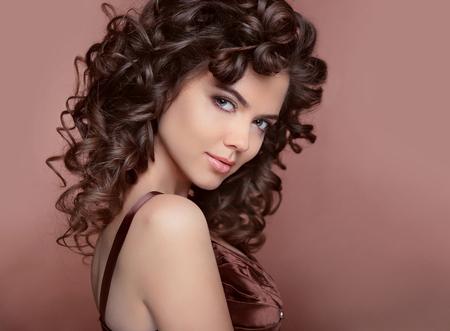 Foto de Healthy hair. Beautiful young smiling woman with long curly hairs. Brunette with professional makeup. - Imagen libre de derechos