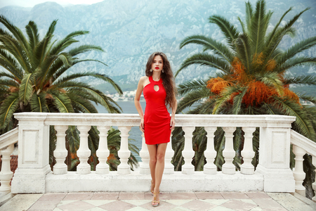 Beautiful young brunette girl model in red dress standing on Balcony view on palms and sea shore Kotor, Montenegro.