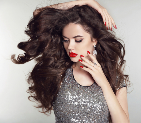 Long hair. Makeup. Beautiful girl portrait. Brunette fashion woman with red lips, manicured nails, healthy curly shiny hairstyle posing on studio background.
