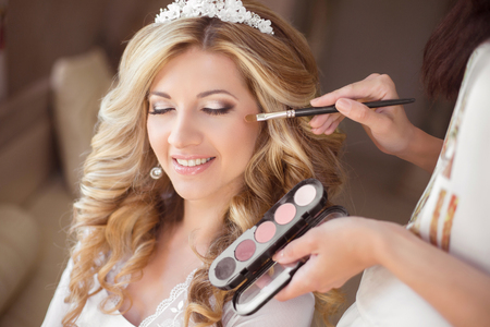 Photo pour Beautiful smiling bride wedding portrait with makeup and hairstyle. Stylist makes make-up girl on wedding day. portrait of young woman at morning. - image libre de droit