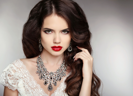 Hairstyle. Makeup. Jewelry. Beautiful woman with curly hair and evening make-up. Beauty fashion girl portrait. Elegant lady with diamond pendant.