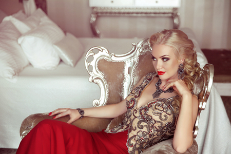 Photo pour Elegant lady. Fashion beautiful sensual blond woman with makeup in luxurious prom dress with bijou, posing on modern armchair with sliver frames. - image libre de droit