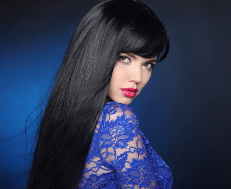 Foto de Long Black Hair. Beautiful model girl with healthy straight shiny hair and sensual lips isolated on blue dark background. Beauty Brunette Woman. - Imagen libre de derechos