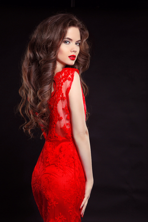 Photo pour Beautiful sexy woman in red fashion dress isolated on black background. Makeup. Beauty Brunette Girl. Healthy Long Hair. - image libre de droit