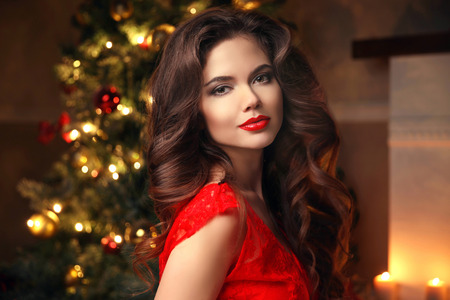 Photo pour Christmas Santa. Beautiful smiling woman model. Makeup. Healthy long hair style. Elegant lady in red dress over christmas tree lights background. happy new year. - image libre de droit