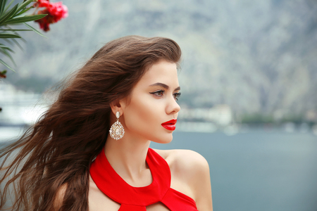 Photo pour outdoor portrait of Beautiful girl with long wavy hair, red lips and fashion earrings. - image libre de droit