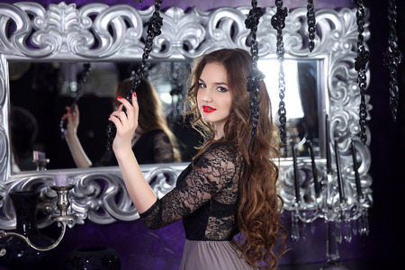 Beautiful smiling young girl with long hairstyle curly hair and red lips