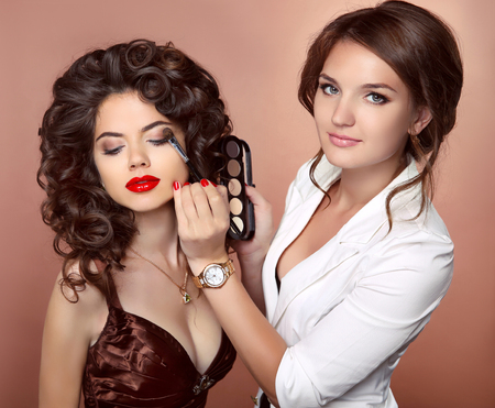 Beauty makeup artist woman applying make up sensual brunette girl model with red lips and shiny curly healthy hair style.の写真素材