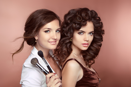 Photo pour Beauty women. Haistyle. Makeup Artist holding brush posing with fashion model. Beautiful two smiling Brunette Girls. Attractive young ladies looking at camera. - image libre de droit