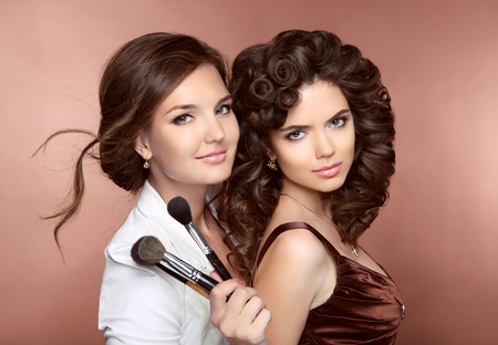 Photo for Hair. Beautiful two Brunette smiling Girls. Makeup artist with brush. Hairstyle. Attractive young women posing at camera. - Royalty Free Image