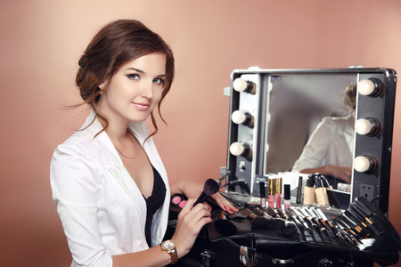 Beauty makeup artist professional stylist holding brushes in dressing drrom. Cosmetics. Attractive Woman face Portrait.