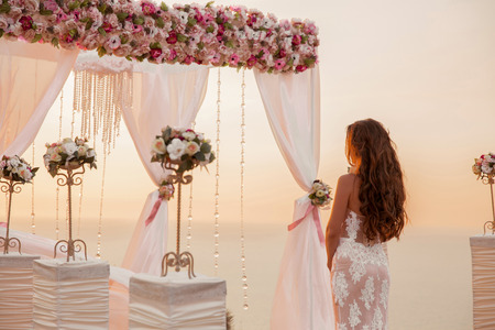 Foto de Wedding ceremony. Brunette bride standing by wreath arch with flower arrangement and white curtain on cliff above sea, outdoor summer photo. Bridal day. Sunset. - Imagen libre de derechos