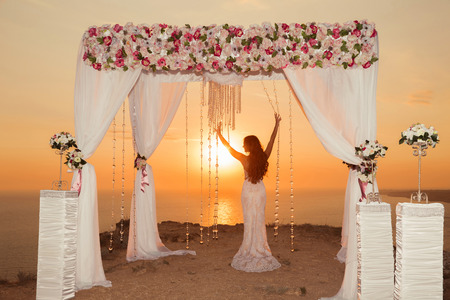 Sunset. bride silhouette. Wedding ceremony arch with flower arrangement and white curtain on cliff above sea, outdoor summer photo.