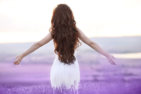 Foto de Free brunette woman with open arms enjoying sunset in lavender field. Harmony. Attractive girl with long curly hair style in white dress dreaming. - Imagen libre de derechos
