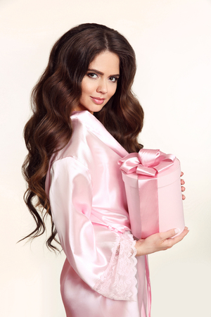 Healthy beauty hair. Pretty smiling brunette girl portrait. Long wavy hairstyle. Attractive young woman holding hat box with pink bow isolated on white studio background. Gift.