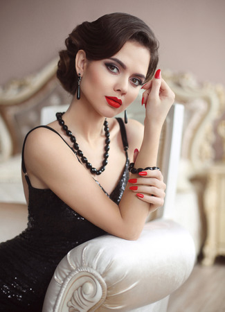 Photo pour Elegant lady. Beauty fashion glamour girl portrait. Sexy brunette with red lips makeup, retro wave hairstyle, manicured nails, expensive black gems jewelry set posing in luxury interior. - image libre de droit
