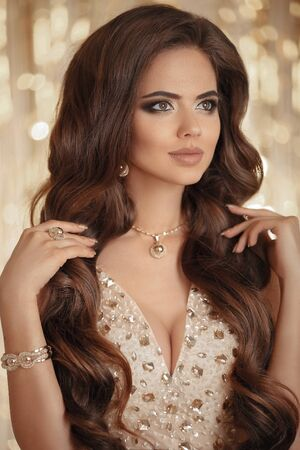 Photo pour Sexy brunette in gold. Fashion Model present Golden Jewelry, Woman Beauty, Beautiful Girl Makeup and Luxury Jewellery. Elegant lady over bokeh lights party. - image libre de droit