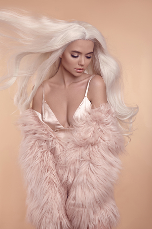 Foto de Beautiful blonde stylish woman in fashion winter clothes. Fashionable sexy girl wearing pink fur coat isolated on beige studio background. Blond Female with blowing healthy long curly hair. - Imagen libre de derechos