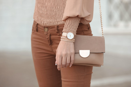 Photo pour Fashion look autumn woman outfit. Stylish women's beige handbag. Closeup of luxury watch and feminine accessories in pastel colored. Cute beige ladies purse bag. - image libre de droit