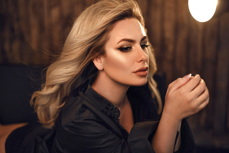 Photo pour Gorgeous model. Blond woman portrait in black shirt. Fashionable girl with beauty makeup and curly hair style posing in wooden dark interior. - image libre de droit