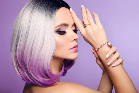 Photo pour Beautiful lady presents amethyst ring and bracelet jewelry set. Woman portrait with ombre bob short hairstyle and manicured nails. Beauty makeup. Gorgeous model isolated on purple background. - image libre de droit