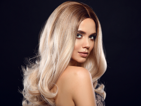 Photo pour Ombre blond curly hair. Beauty fashion blonde woman portrait. Beautiful girl model with makeup, long healthy hairstyle posing isolated on studio black background. - image libre de droit