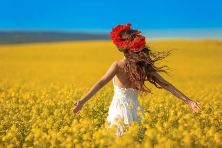 Foto de Beautiful young woman with long healthy hair over Yellow rape field landscape background. Attracive brunette girl with red poppy wreath on hairstyle, outdoor portrait. Natural beauty. - Imagen libre de derechos