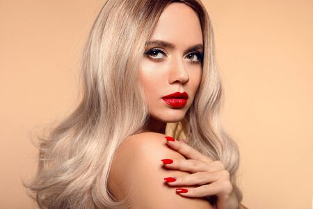 Photo pour Beauty portrait of blonde woman with red lips, long healthy shiny blond hair style and manicured nails looking at camera. Sensual girl with bright makeup isolated on beige backhround. - image libre de droit