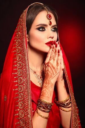 Photo pour Portrait of beautiful indian girl in red bridal sari. Young hindu woman model with kundan jewelry set. Traditional Indian costume lehenga choli. Henna painting, mehendi on bride's hands. - image libre de droit