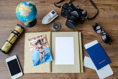 Photo pour Notepad, credit cards, passport, ticket, luggage, phone and compass on a wooden background, set for travel planning - image libre de droit
