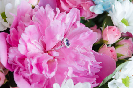 Photo for ring with a blue stone in a pink peony, a gift for the holiday, close-up - Royalty Free Image